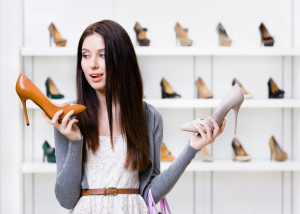 Woman avoiding foot pain by picking shoes